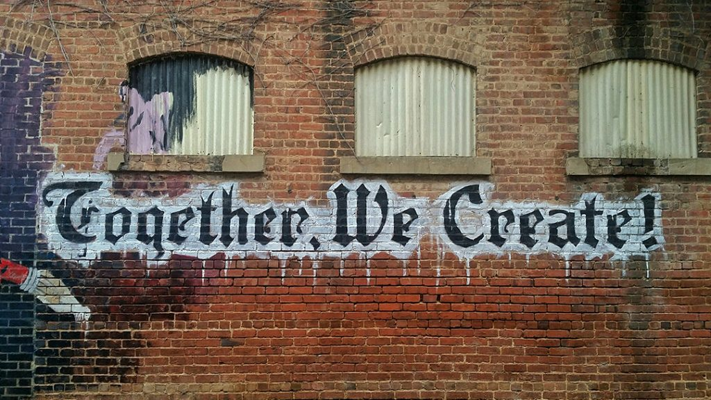 Stellen Design graphic design firm shares on working with a graphic designer with an image of a together we create spray painted on the side of a wall